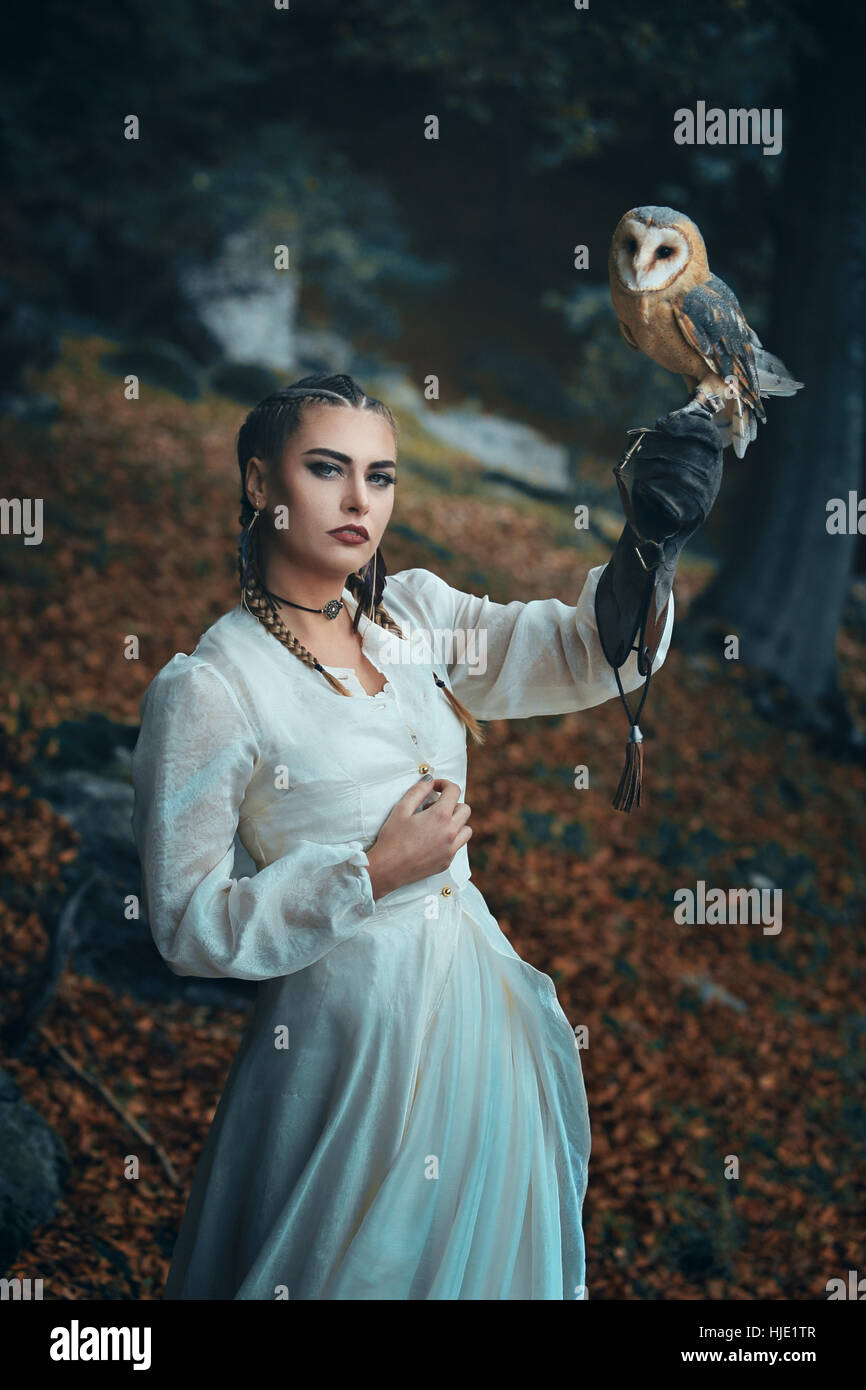 Elegant gekleidete Frau mit Schleiereule. Fantasie und Falknerei Stockfoto