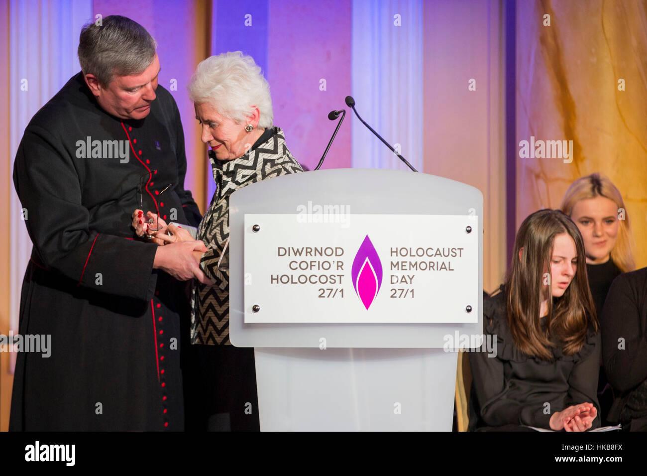 Cardiff, Wales, Großbritannien. 27. Januar 2017.  Holocaust-Überlebende Eva Clarke wird unterstützt durch The Reverend Stockfoto