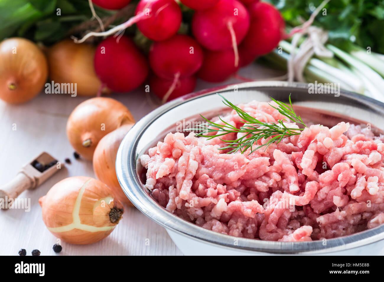 Rohes Hackfleisch in weiße Schüssel. Hackfleisch vom Schwein auf einem Hintergrund von frischem Bio-Gemüse Stockbild