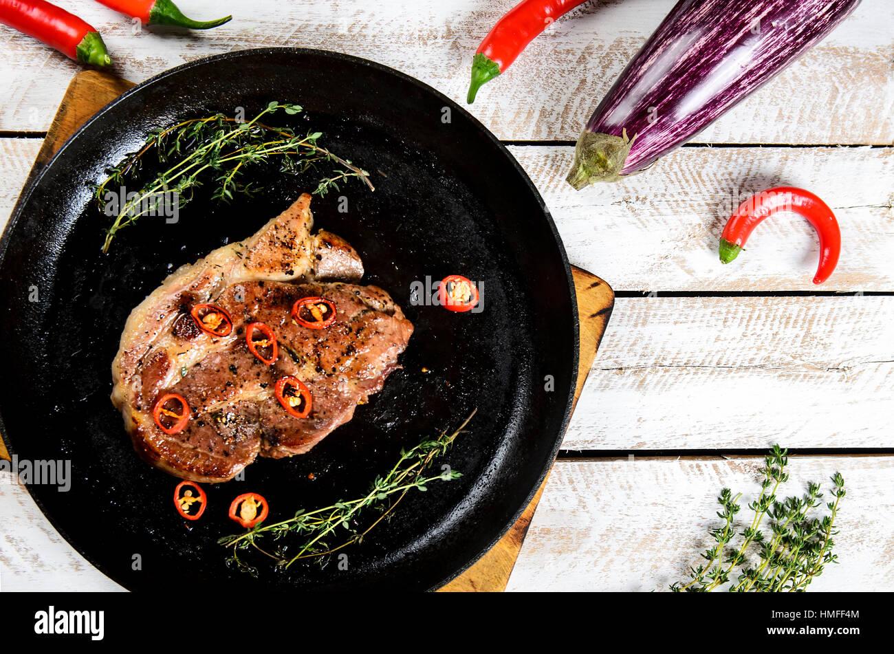 Fleisch mit Gewürzen in einer Pfanne, Rosmarin und hot Chili Peppers auf einem weißen Holztisch Hintergrund Stockbild