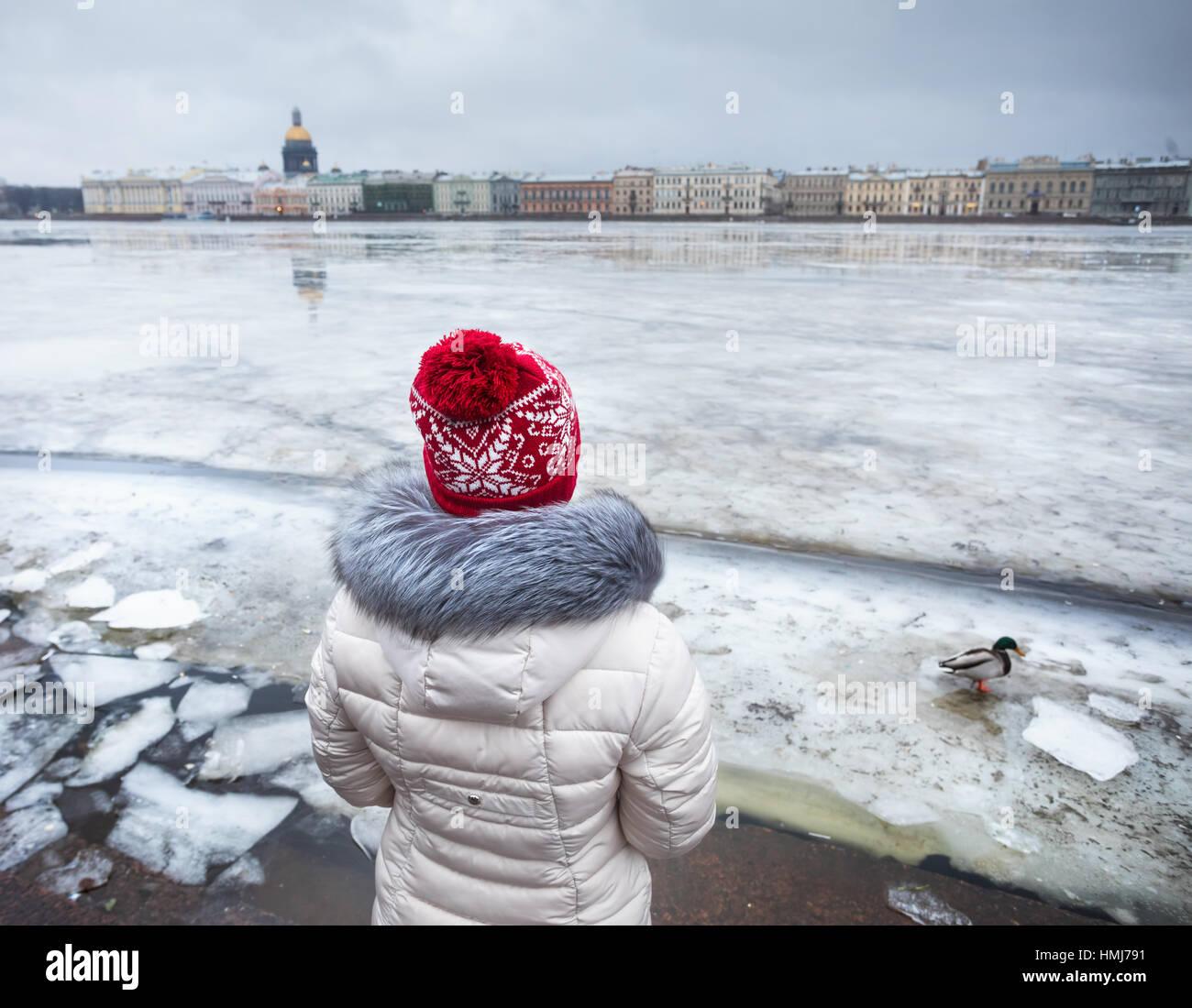 Frau im roten Hut in der Nähe von zugefrorenen Newa mit Ente und Isaak Kathedrale auf der anderen Seite im Stockbild