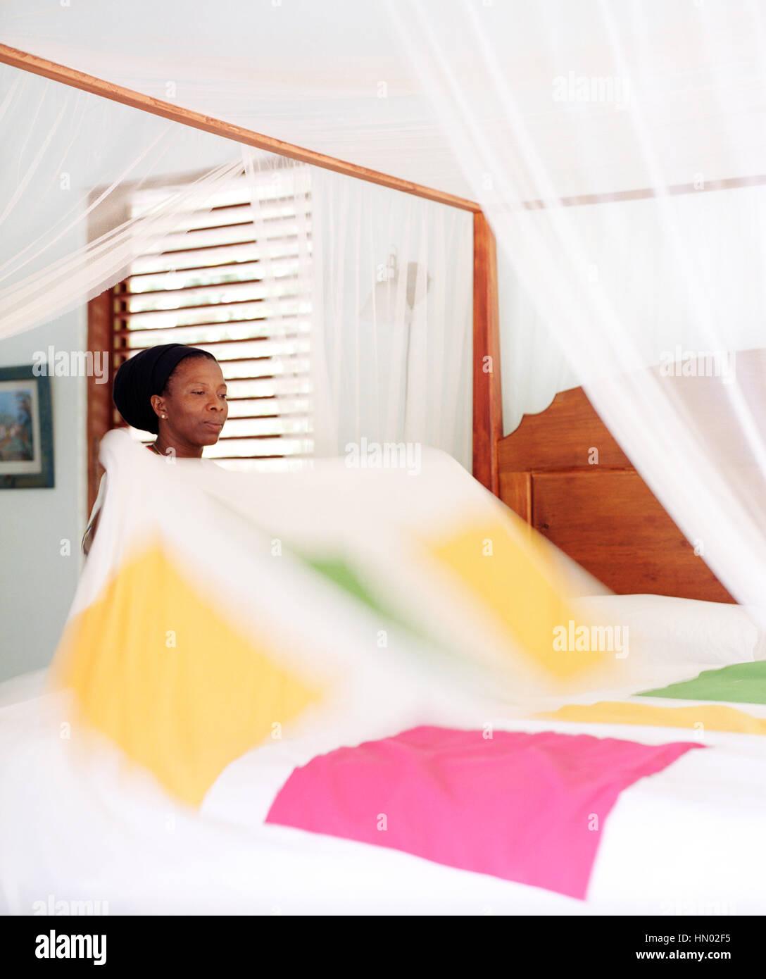 Eine Haushälterin macht ein Bett in der Hibiscus Villa im Steinfeld Estate Villa Resort in St. Lucia. Soufrière, Stockbild