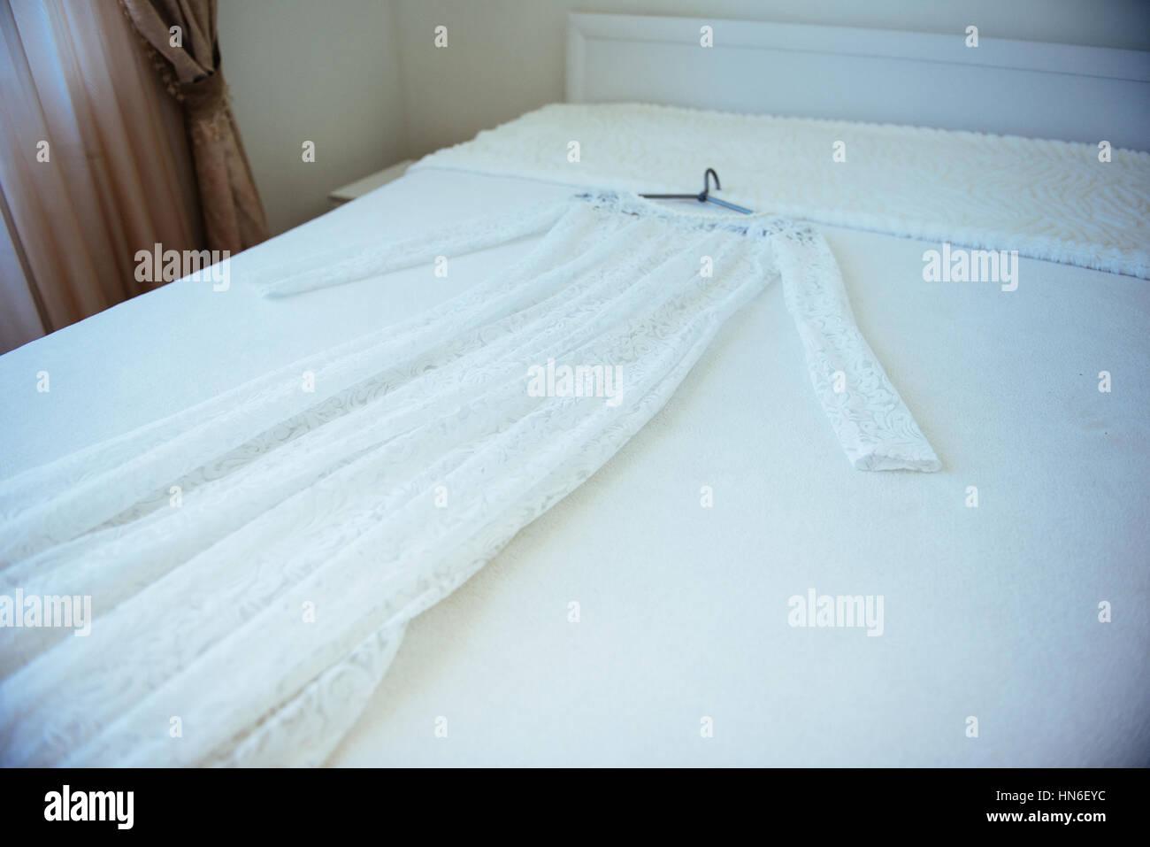 Brautkleid mit Aufhänger mit auf dem Bett Stockbild