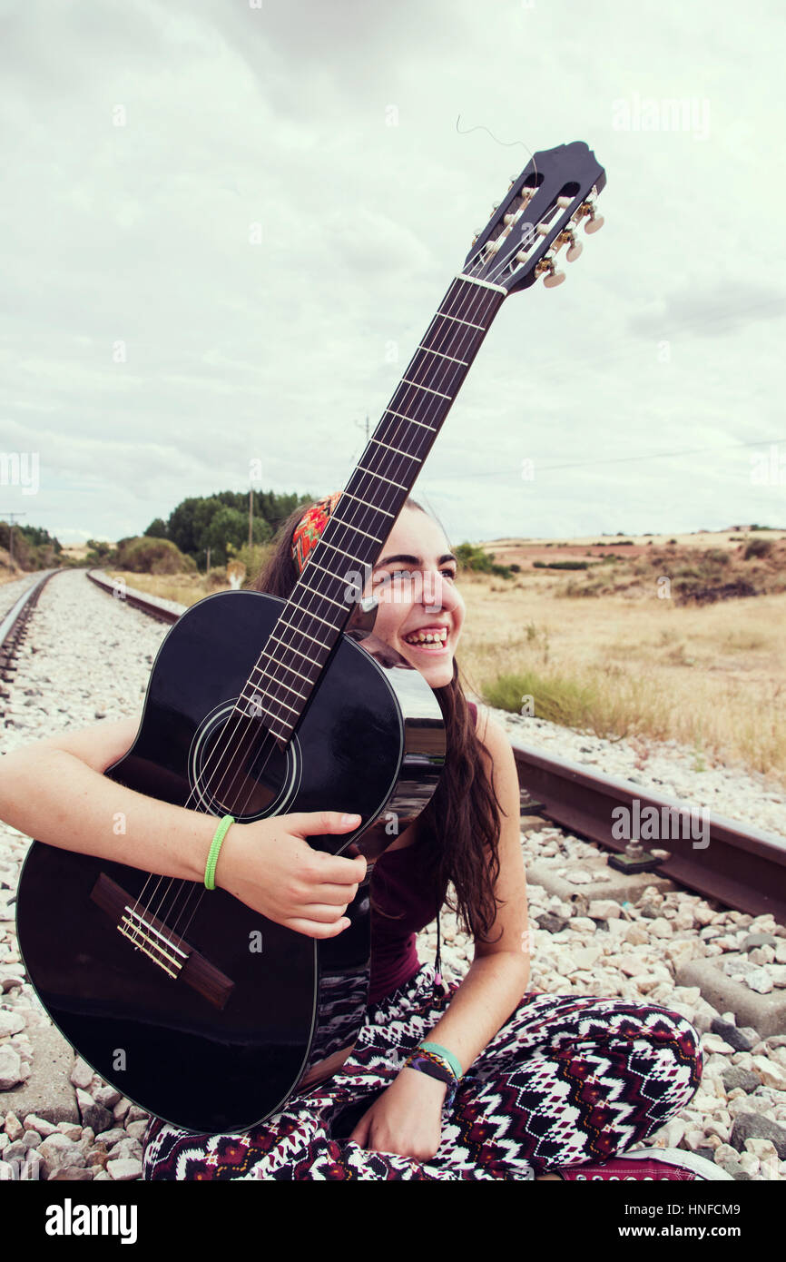 Teen Frau gewissermaßen Eisenbahn mit ihrer Gitarre Stockbild