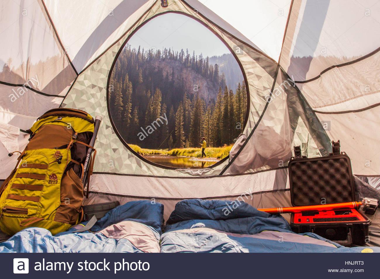 Ein Blick aus dem Inneren des Zeltes an einem Mann Fliegenfischen. Stockbild