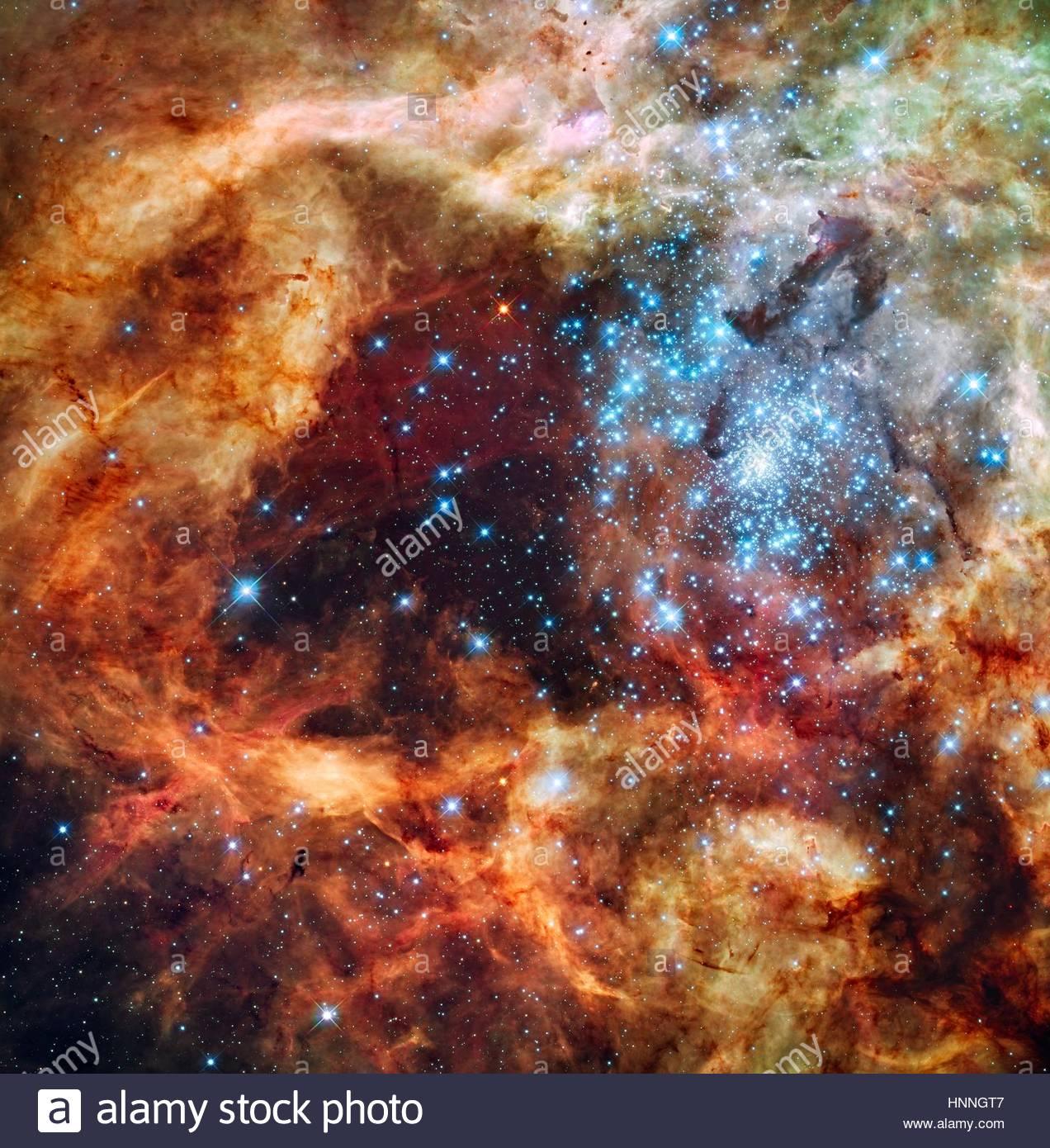 Sekt mit Energie, leuchtet eine Gruppe von jungen Sternen ein Hohlraum in den aufgewühlten Staub von den Tarantelnebel. Stockbild