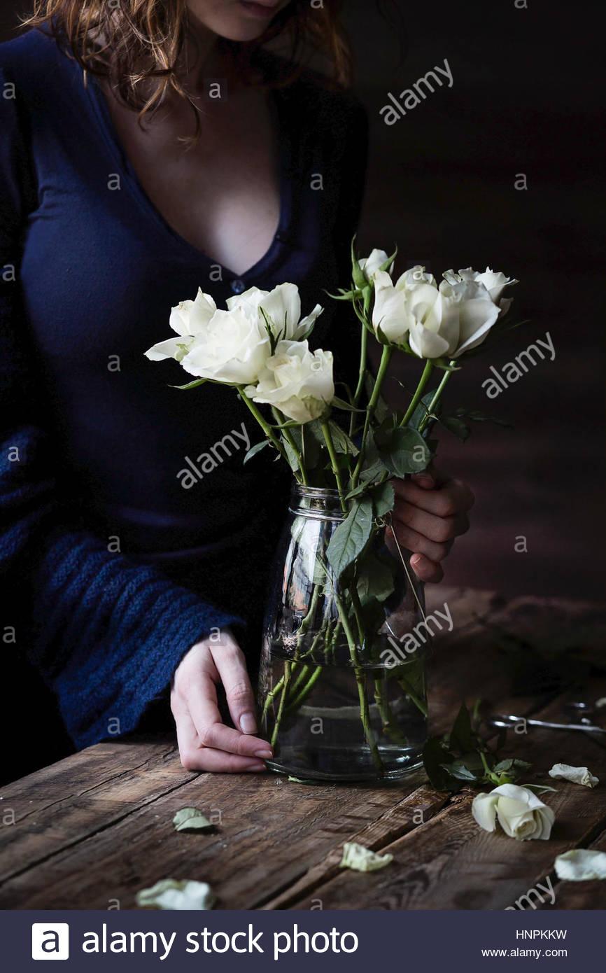 Weiße Rosen auf Holztisch und Frau im Hintergrund Stockbild