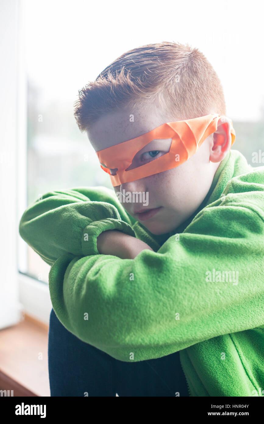 Ein 10 Jahre alter Junge gekleidet wie ein Superheld in einer orange-Maske. Stockbild