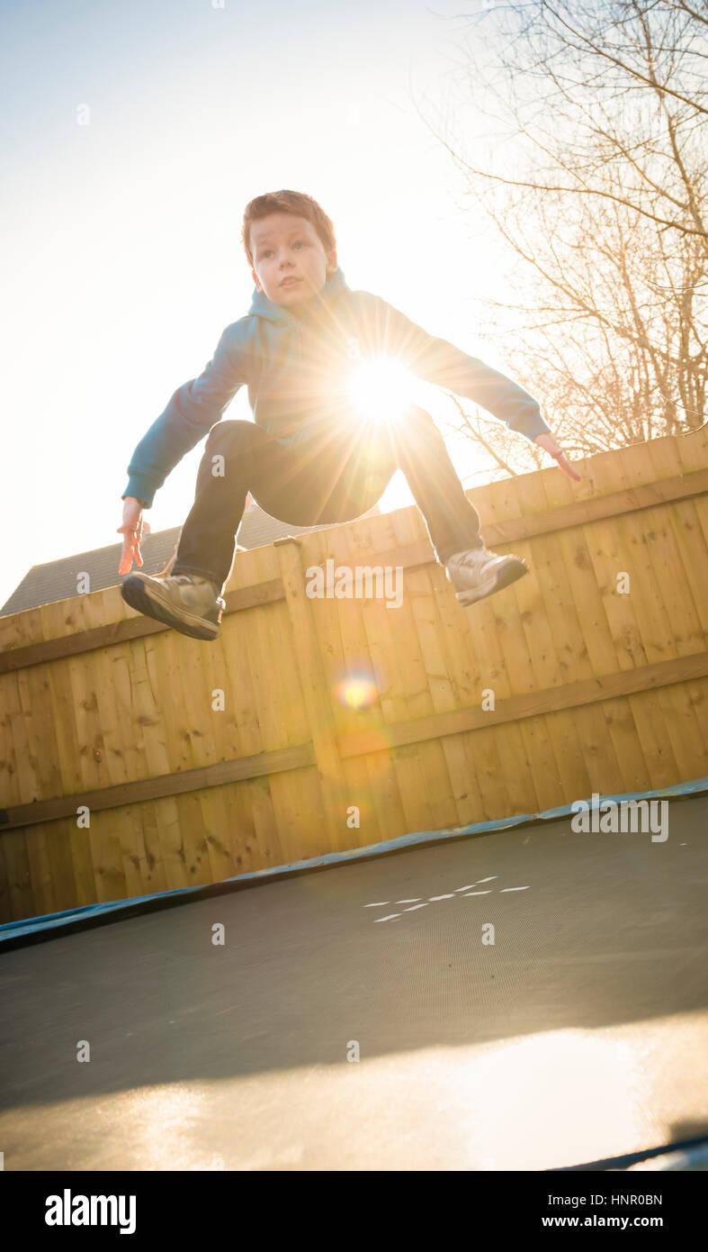 9-jähriger Junge springen auf einem Trampolin in seinem Garten. Stockbild