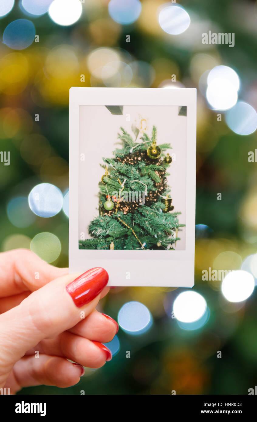 Frau mit einem sofortigen Druck eines Weihnachtsbaumes vor dem Baum Stockbild
