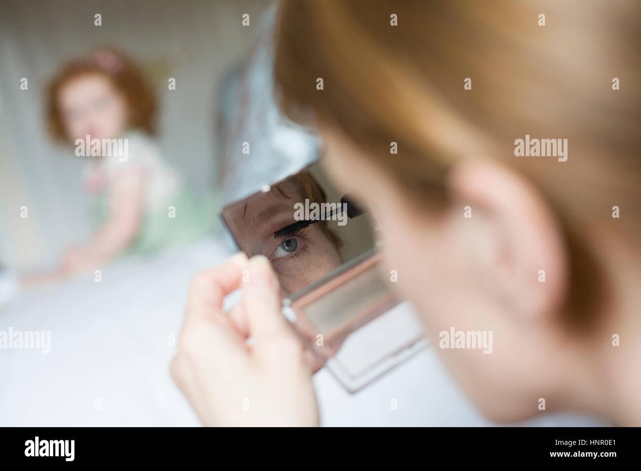 Eine Frau, die die Anwendung bilden, während ihre Tochter Uhren Stockbild
