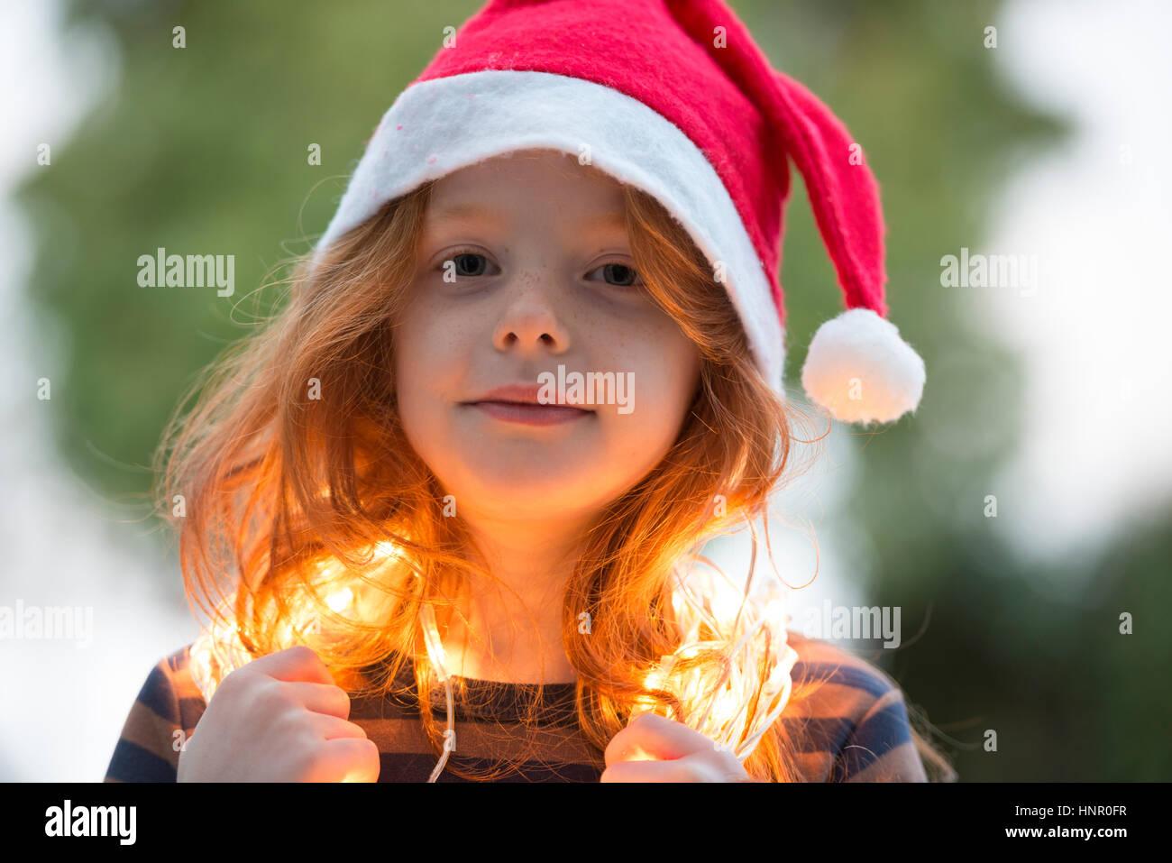 Ein kleines Mädchen gekleidet in einem Santa Hut und Fee Weihnachtsbeleuchtung Stockbild