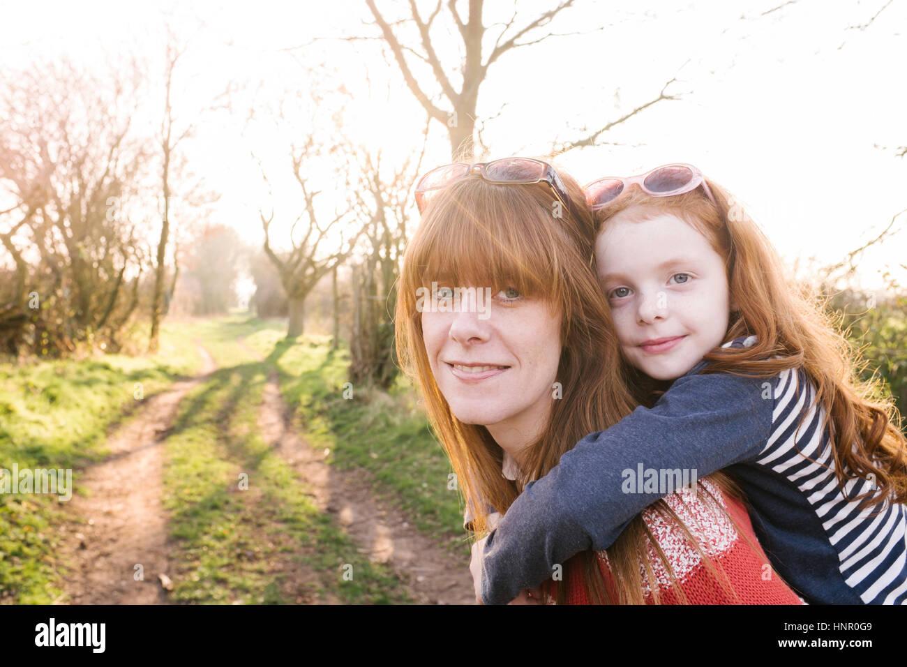 Ein kleines Mädchen gegeben einen Huckepack-Lift von der Mutter während eines Spaziergangs auf dem Lande Stockbild