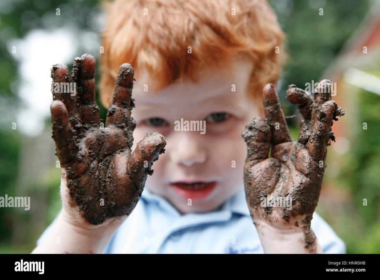 Ein Kind hält seinen schlammigen Hände Stockbild