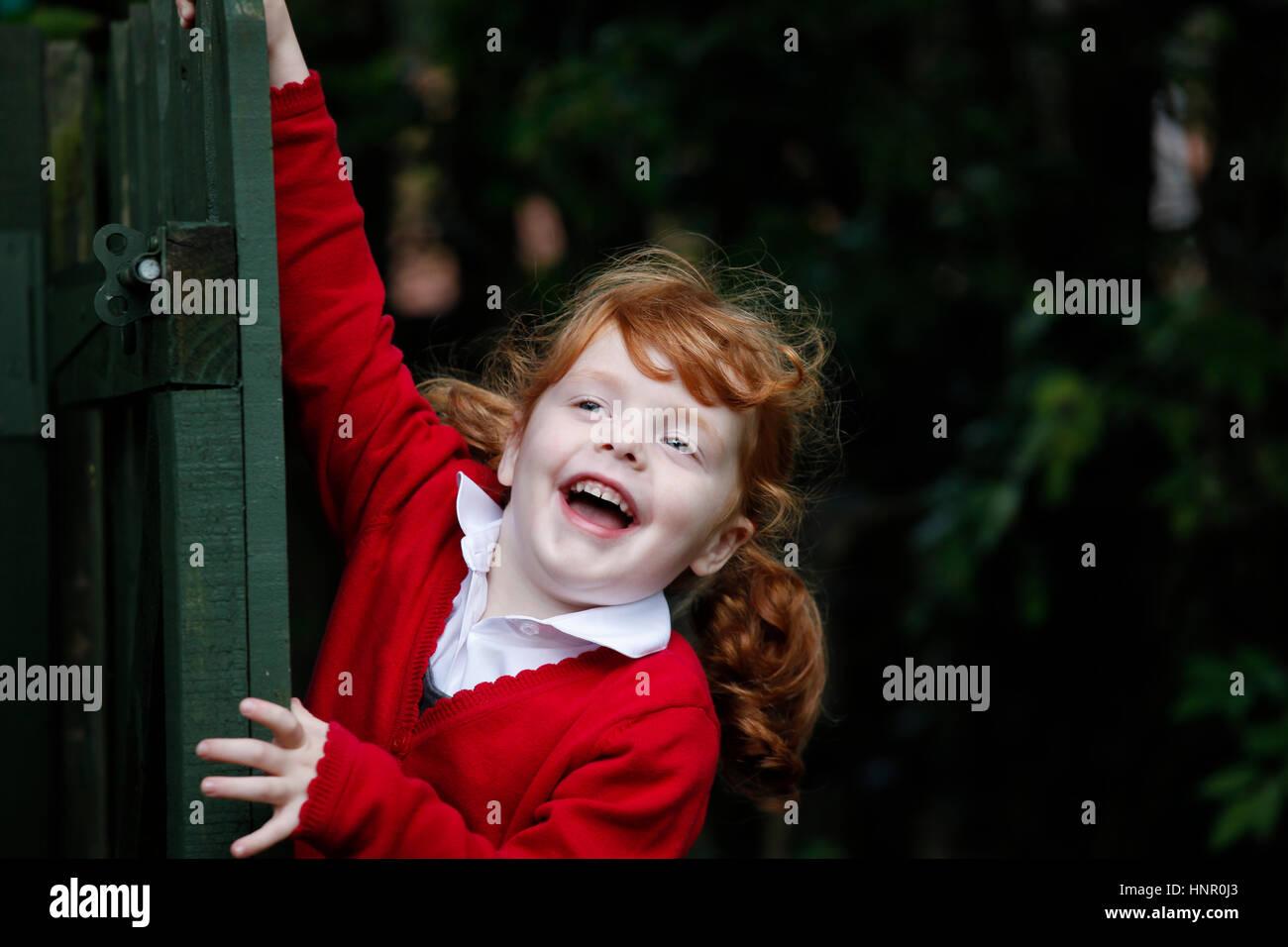 Kleines Mädchen, 4 Jahre, tragen ihre Schuluniform in einem Garten. Stockbild