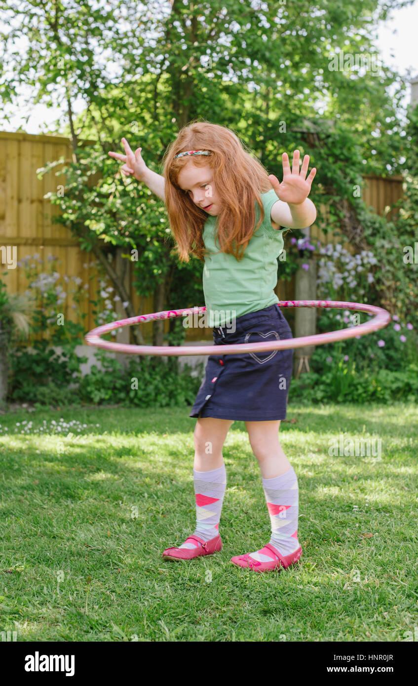Kleine Mädchen spielen mit einem Hula-Hoop in ihrem Garten Stockbild