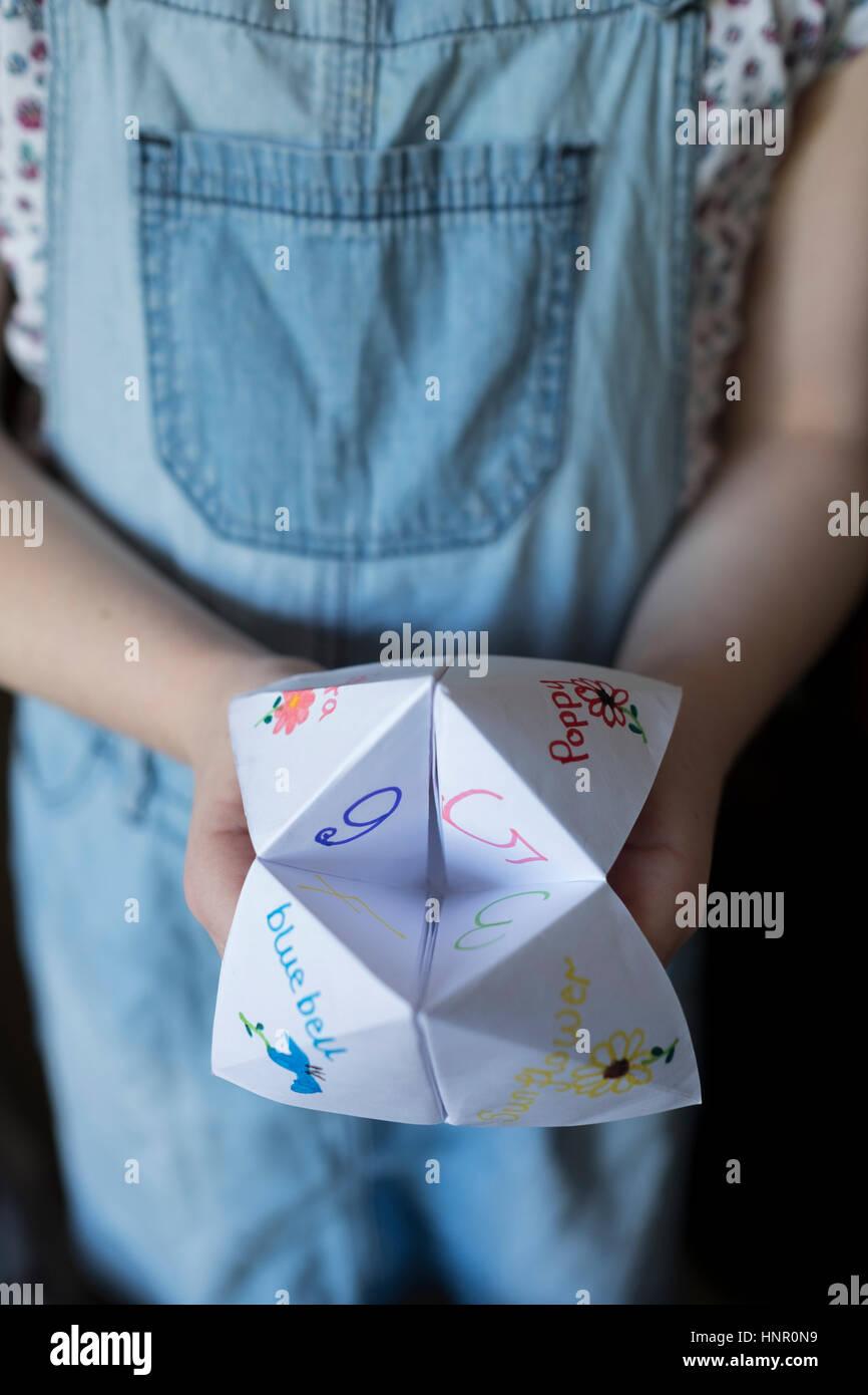 Ein Mädchen mit einer Wahrsagerin Origami-Papier-Spiel Stockbild