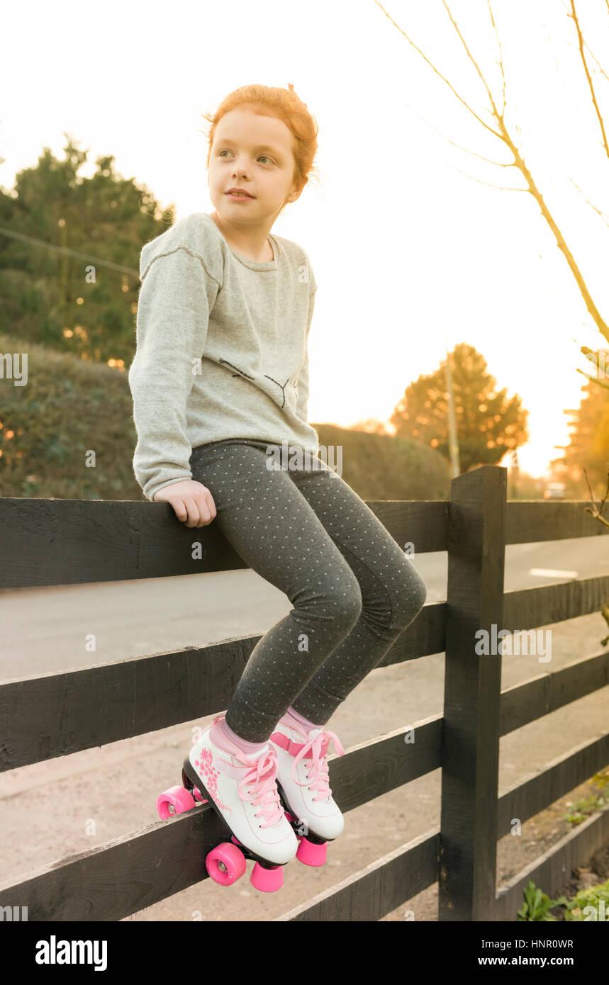 Ein kleines Mädchen sitzt auf einem Zaun in Rollschuhe Stockbild