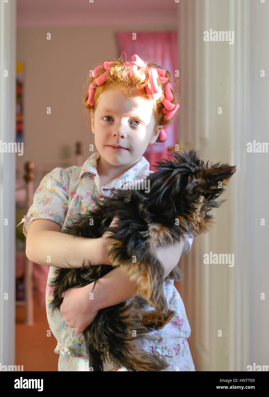 Ein kleines Mädchen in Rollen, die mit ihrem Hund Stockbild