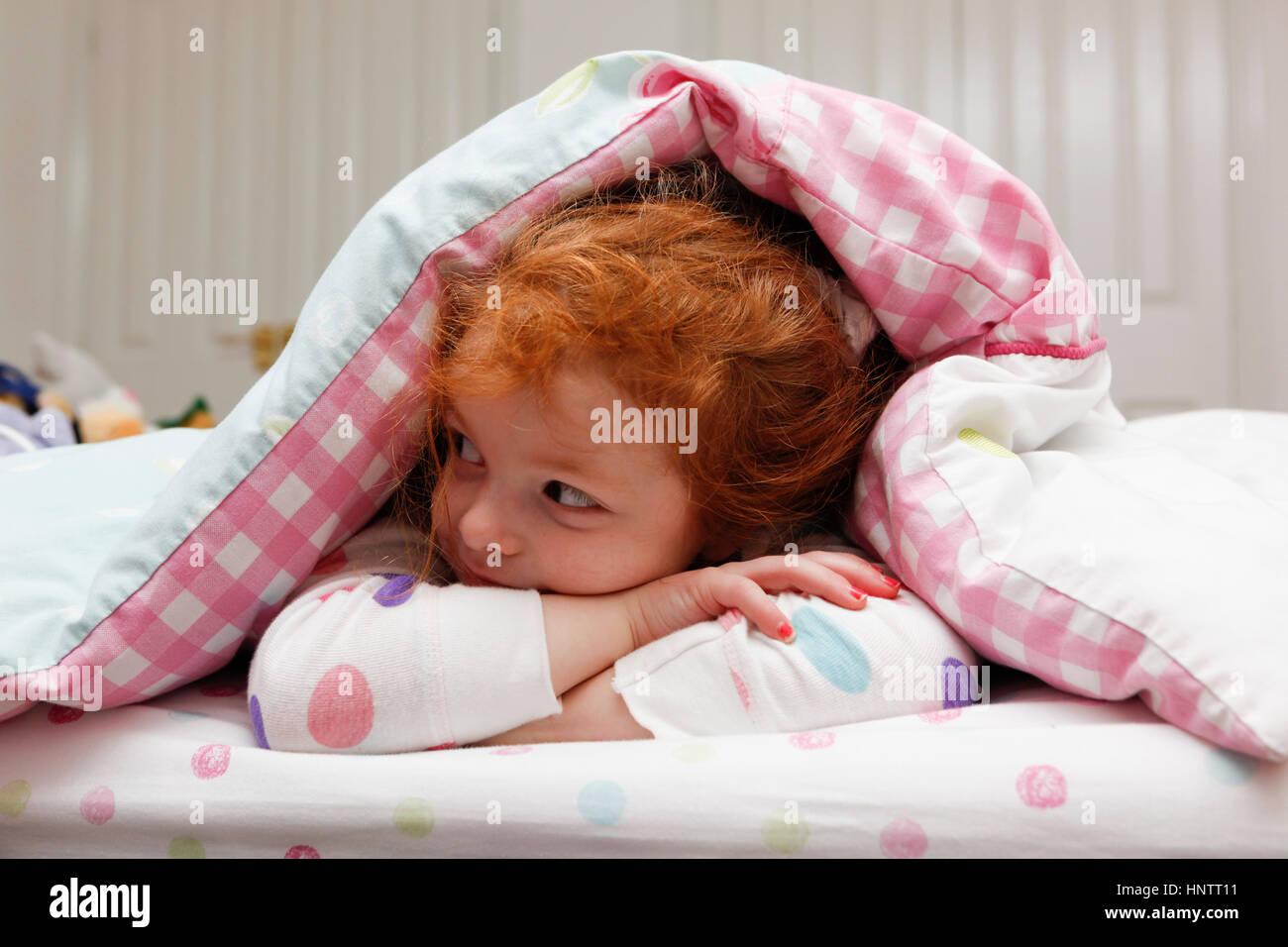 Kleines Mädchen wach im Bett. Stockbild