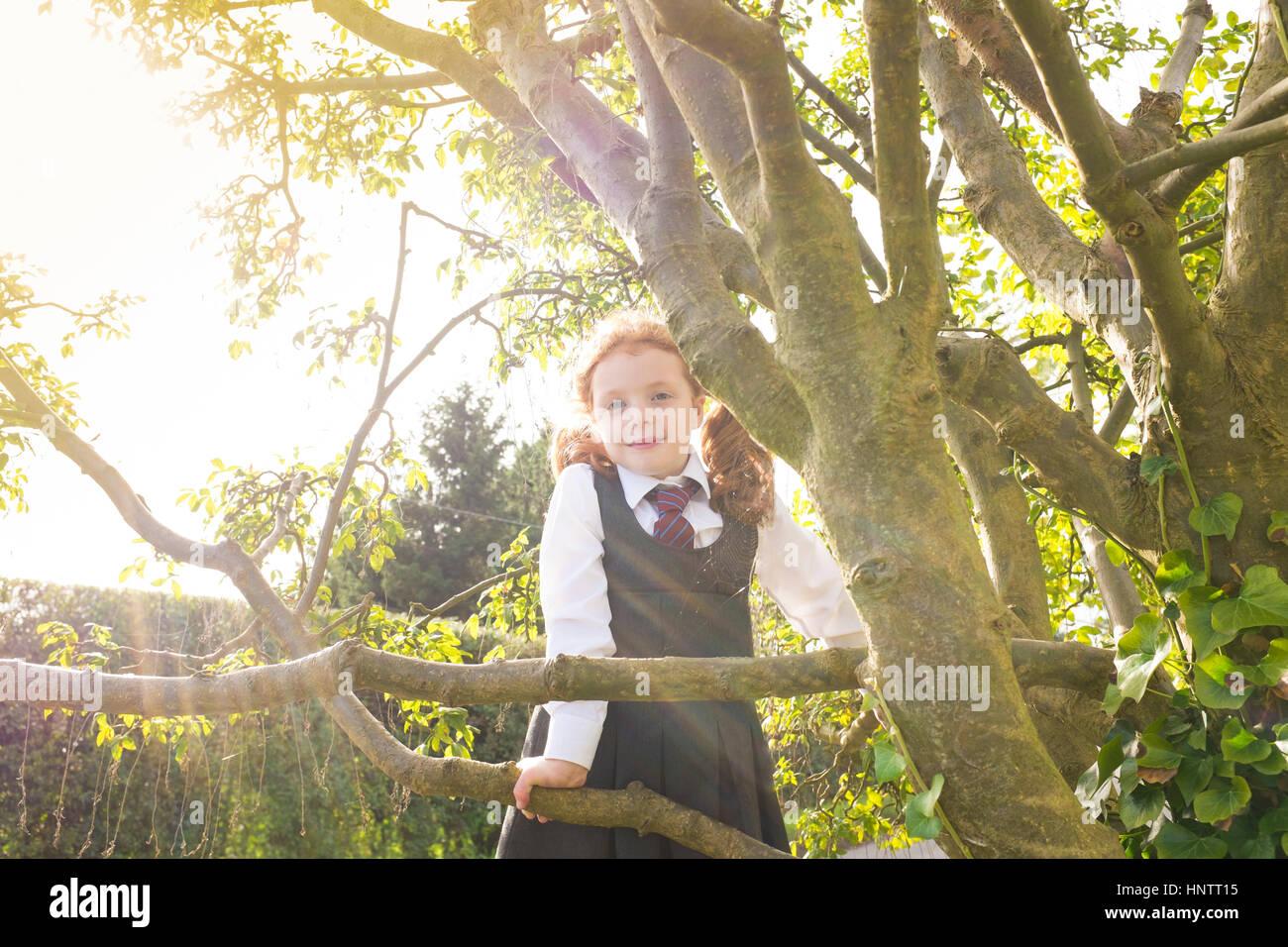 Ein kleines Mädchen einen Kletterbaum in ihrer Schuluniform. Stockbild