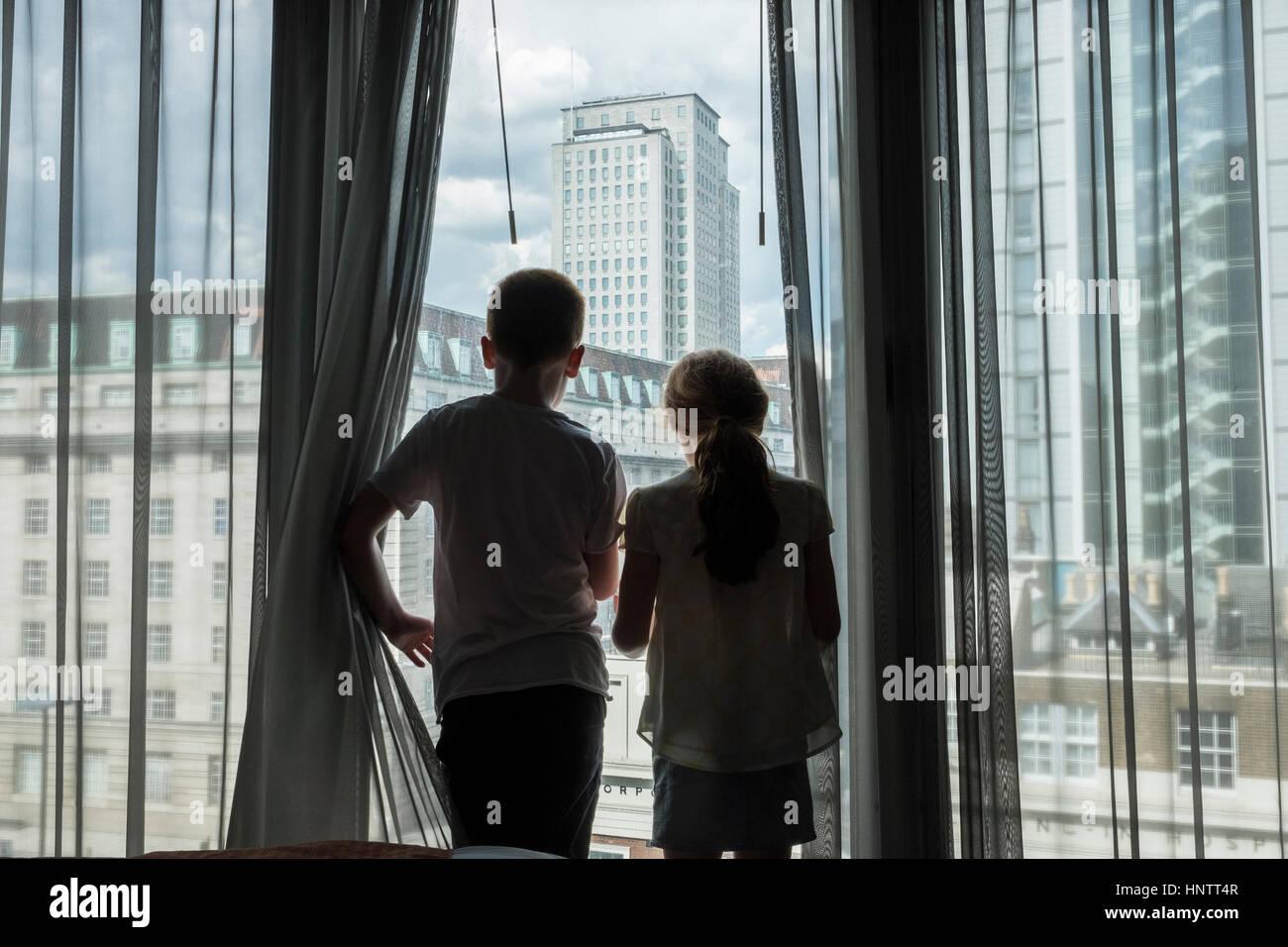 Ein Junge und Mädchen, die durch ein hohes Fenster in einer Stadt suchen. Stockbild