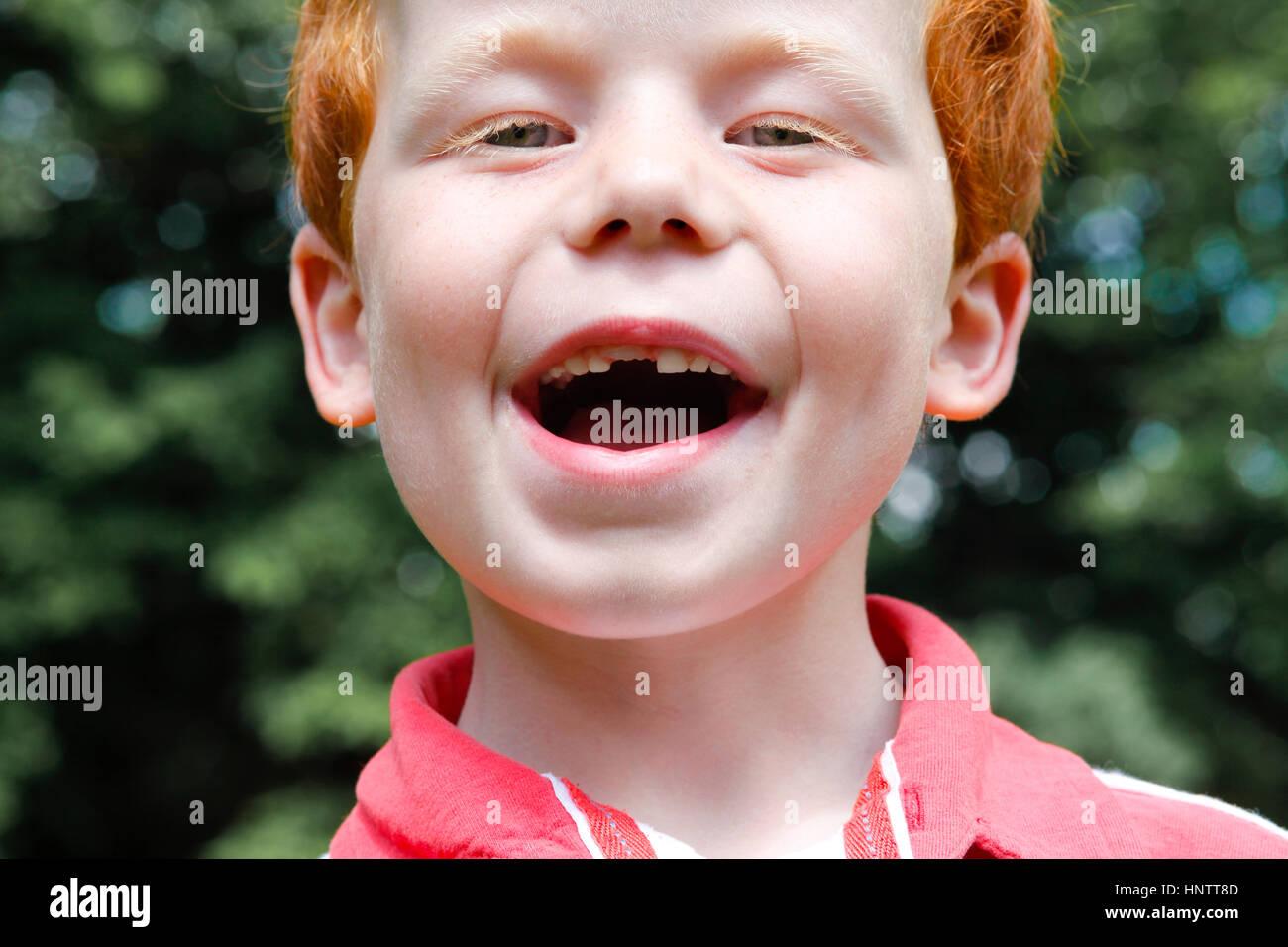 Ein sechs yeal Alter junge lächelt zeigt seine fehlenden Kind Zahn und seinen Erwachsenen Zahn durch, im Garten Stockbild