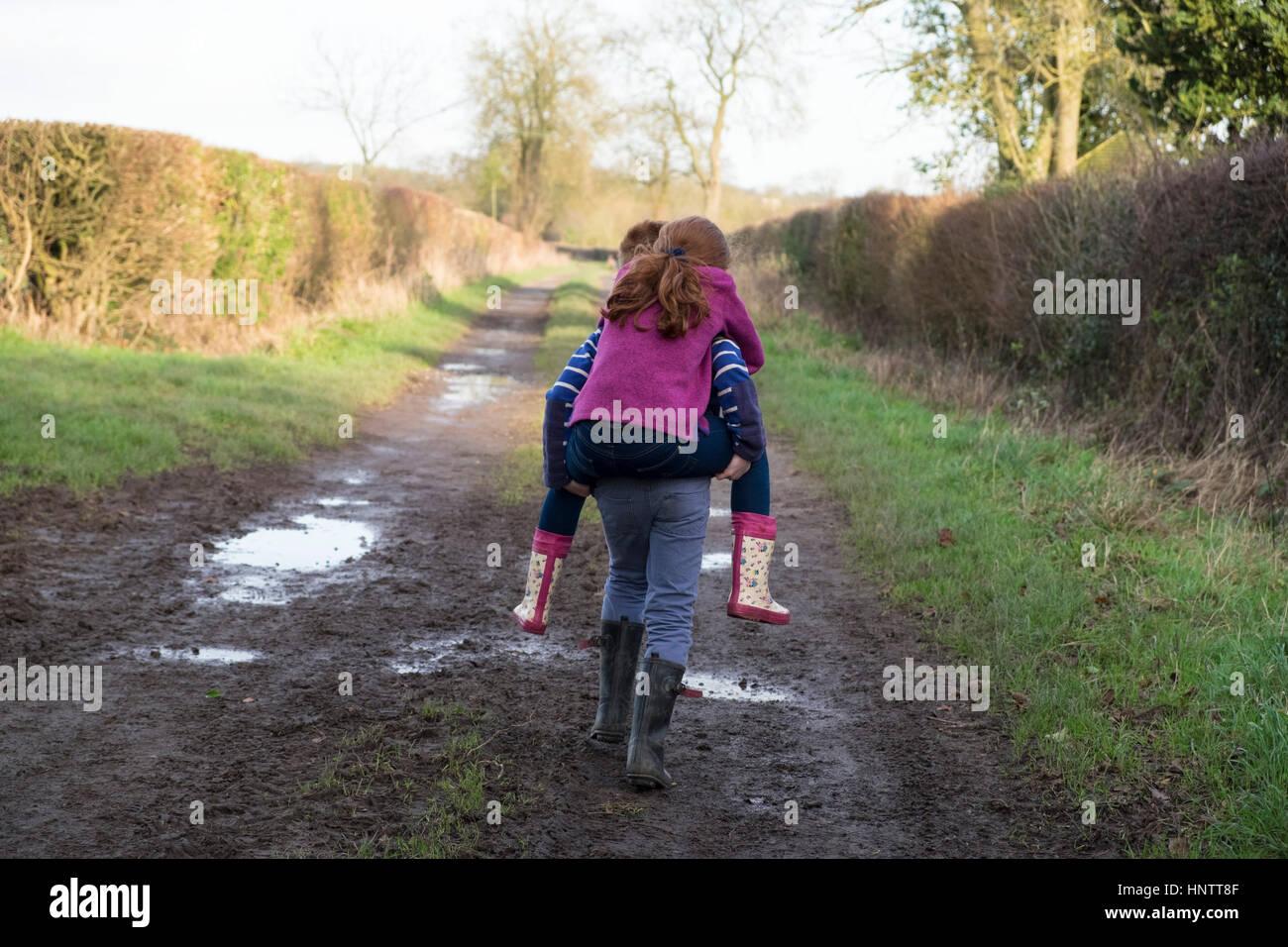 Ein kleines Mädchen von ihrem Bruder auf dem Land getragen werden. Stockbild
