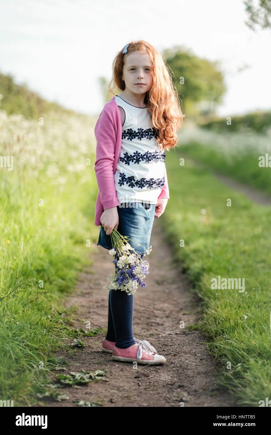 Ein kleines Mädchen im grünen Blumen zu pflücken. Stockbild