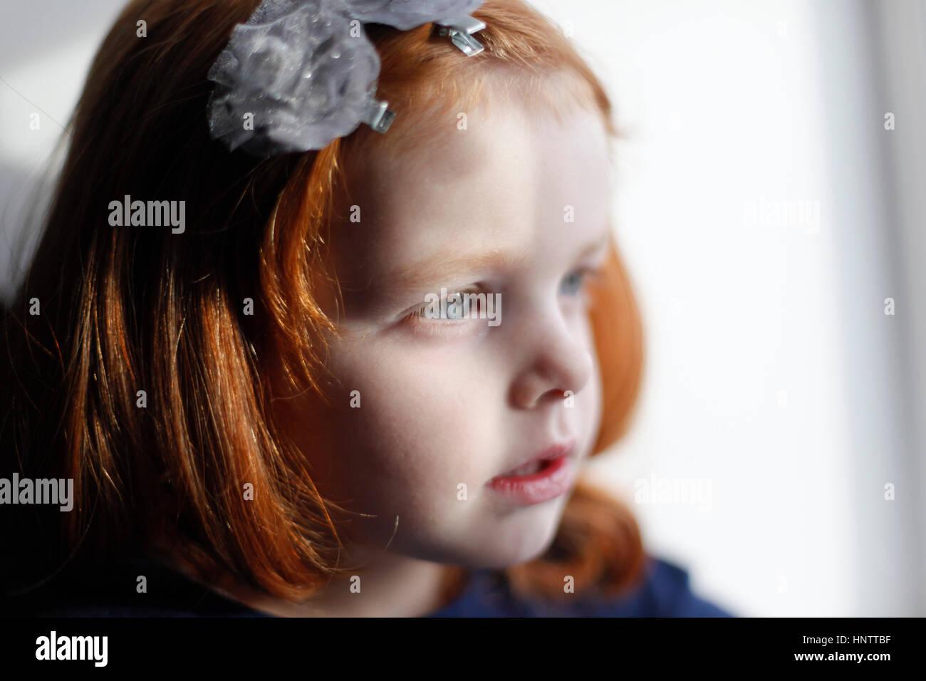Ein 4 Jahre altes Mädchen mit Ingwer Haar sieht aus dem Fenster Stockbild