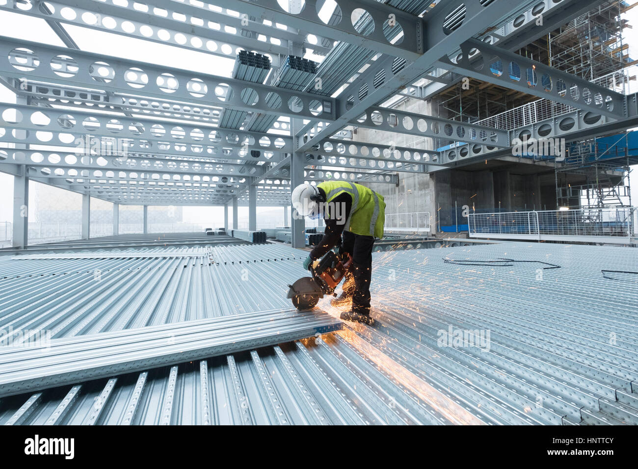 Workman schneiden Stahl Bodenbelag auf einer Baustelle in Schutzkleidung Stockbild
