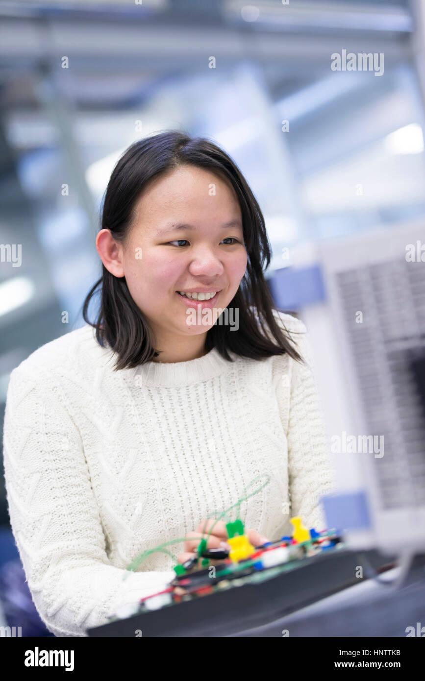 Eine Frau-Ingenieur arbeitet mit Elektronik Stockbild