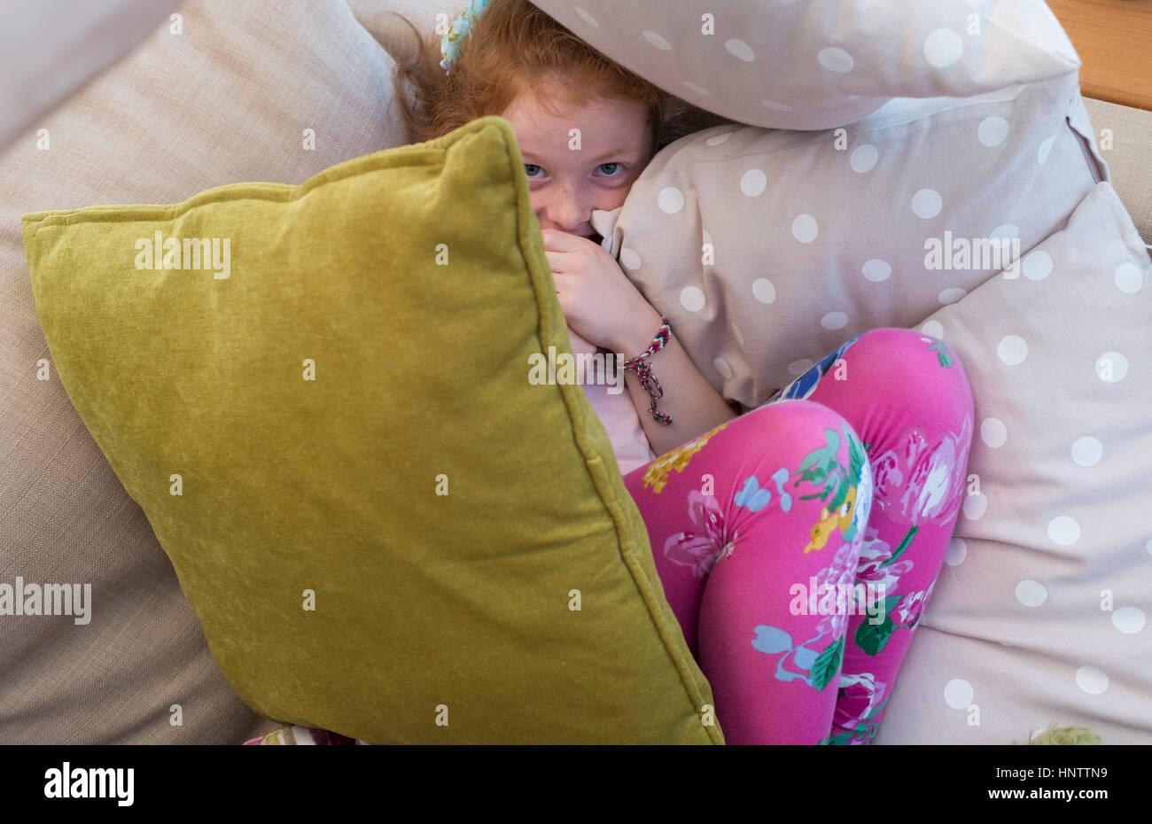 Ein kleines Mädchen versteckt sich unter einigen Kissen Stockbild