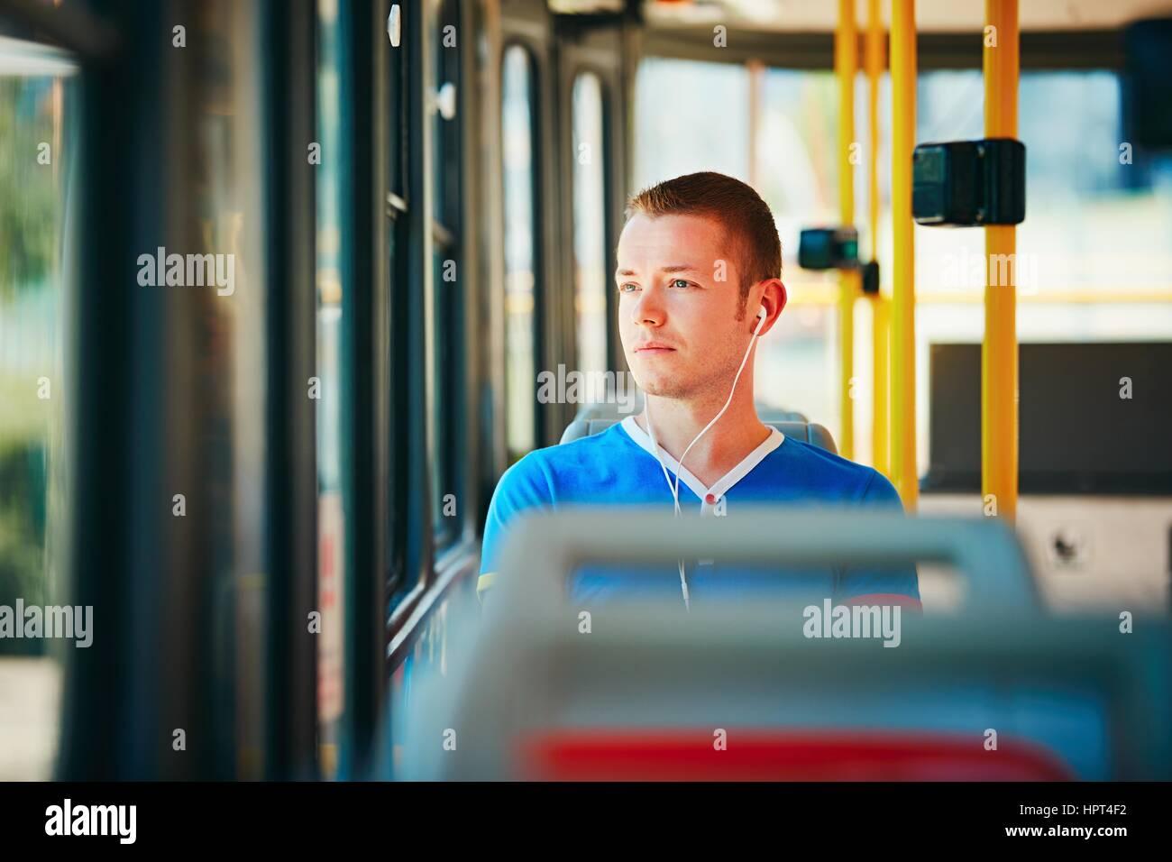 Einsamkeit-Mann trägt Kopfhörer und Musik hören. Alltag und pendeln zur Arbeit mit öffentlichen Stockbild
