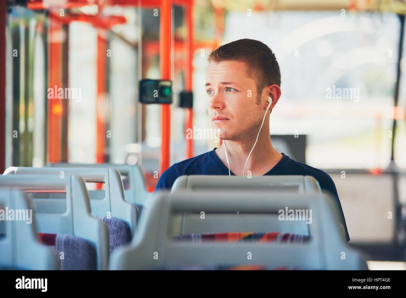 Trauriger junger Mann reist mit der Straßenbahn (Bus). Alltag und pendeln zur Arbeit mit öffentlichen Stockbild