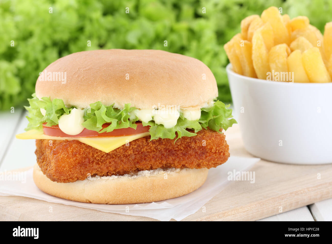 Fisch burger fishburger Hamburger mit Pommes frites Tomaten Salat Käse ungesund Stockbild