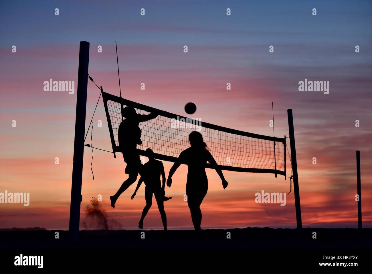 Silhouetten von weiblichen Volleyballspieler üben Volleyball am Strand bei Sonnenuntergang in Mission Beach, Stockbild