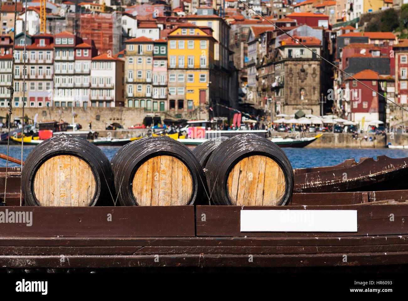 Detail des Portweins Fässer in einem Boot in den Fluss Douro mit der Stadt Porto im Hintergrund Stockbild