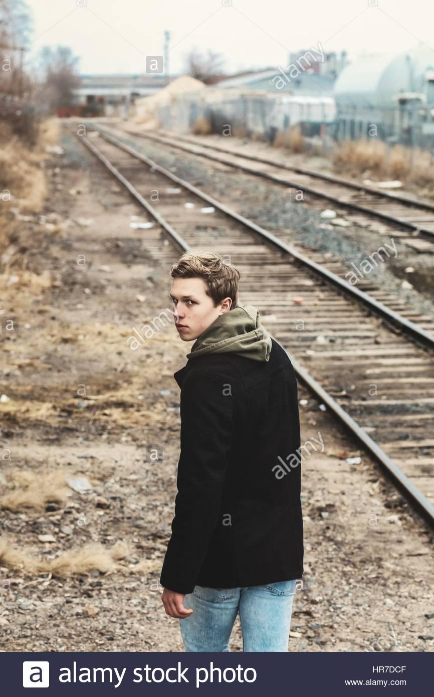 Junger Mann zu Fuß entfernt, in der Nähe von Eisenbahnschienen Stockfoto