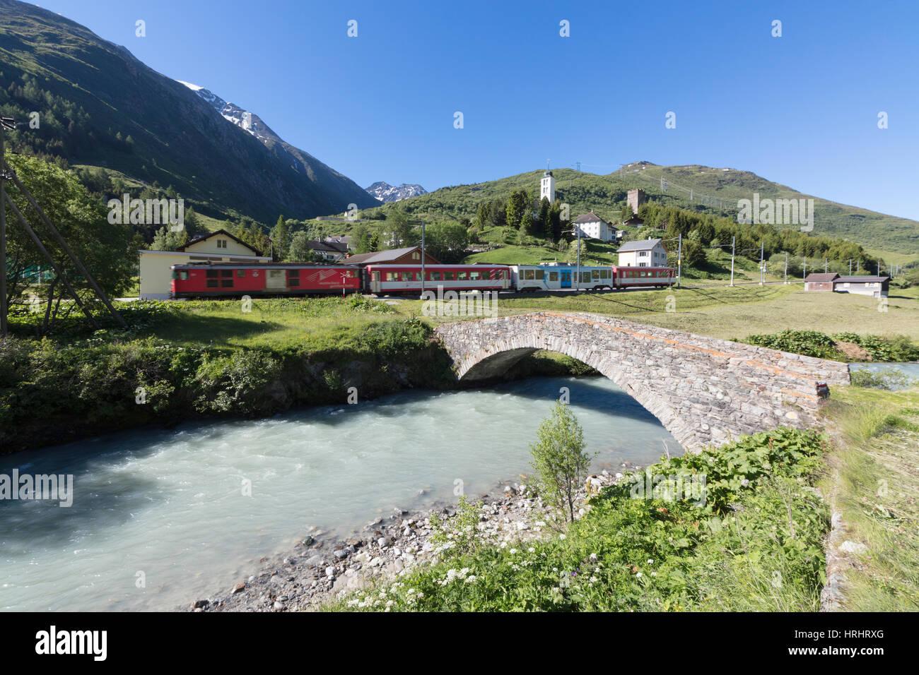 Typische rote Schweizer Schulen an Hospental Viadukt umgeben von Creek und grüne Wiesen, Andermatt, Kanton Stockbild