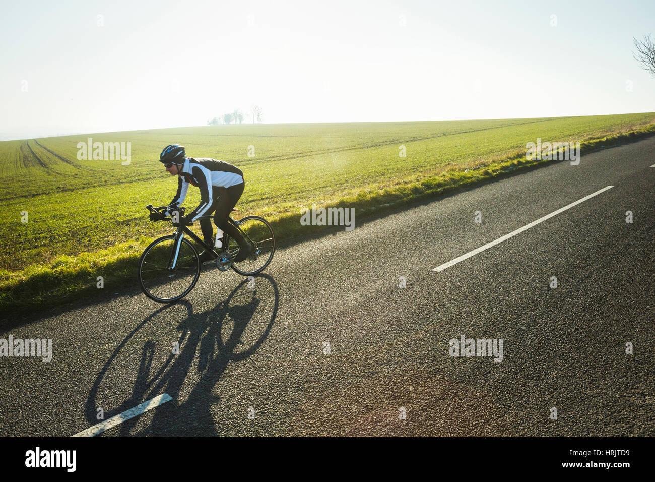 Ein Radsportler entlang einer Landstraße, an einem klaren sonnigen Wintertag. Schatten Sie auf der Fahrbahn. Stockbild