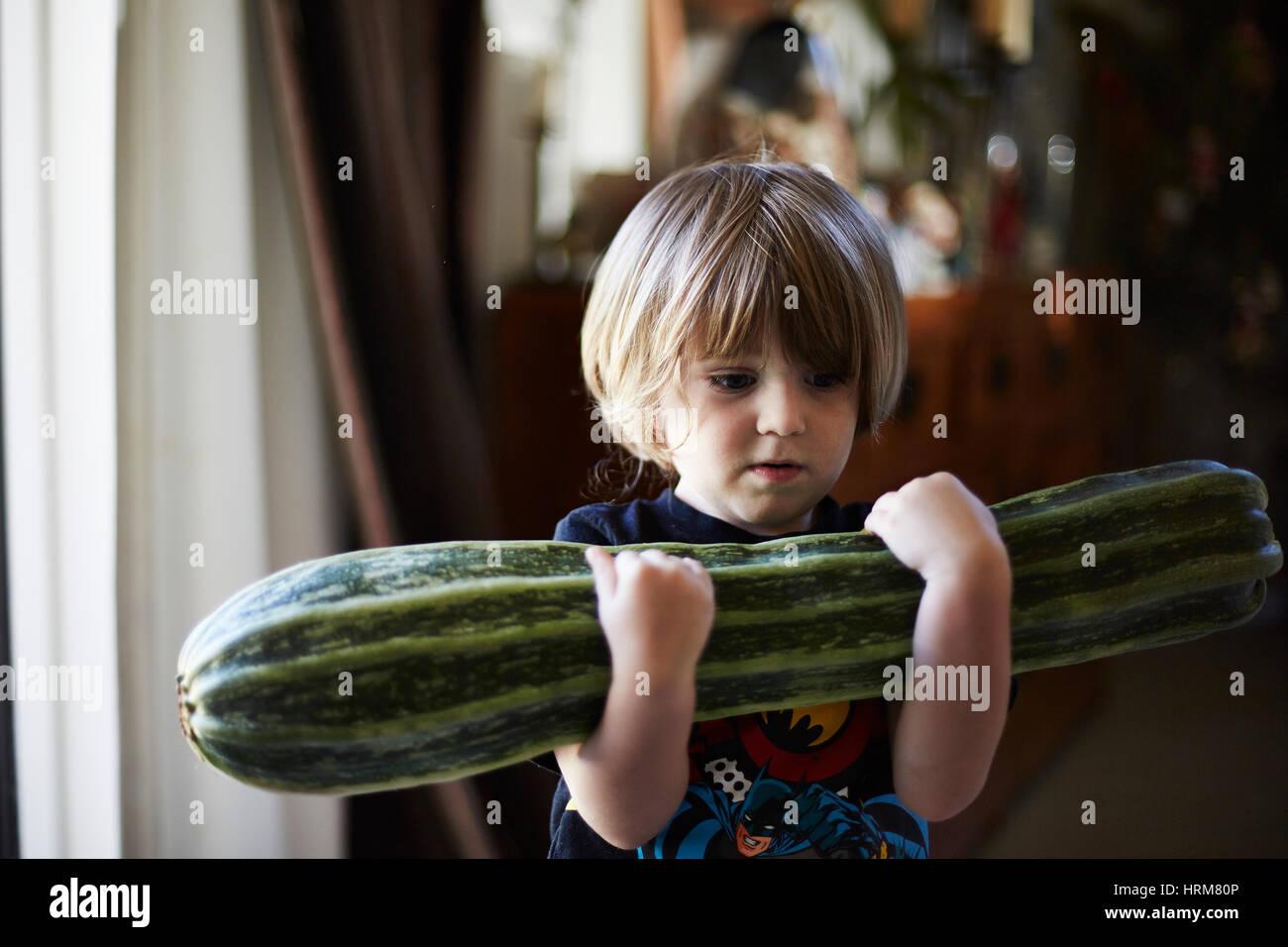 Kleiner Junge mit großen Zucchini Stockbild