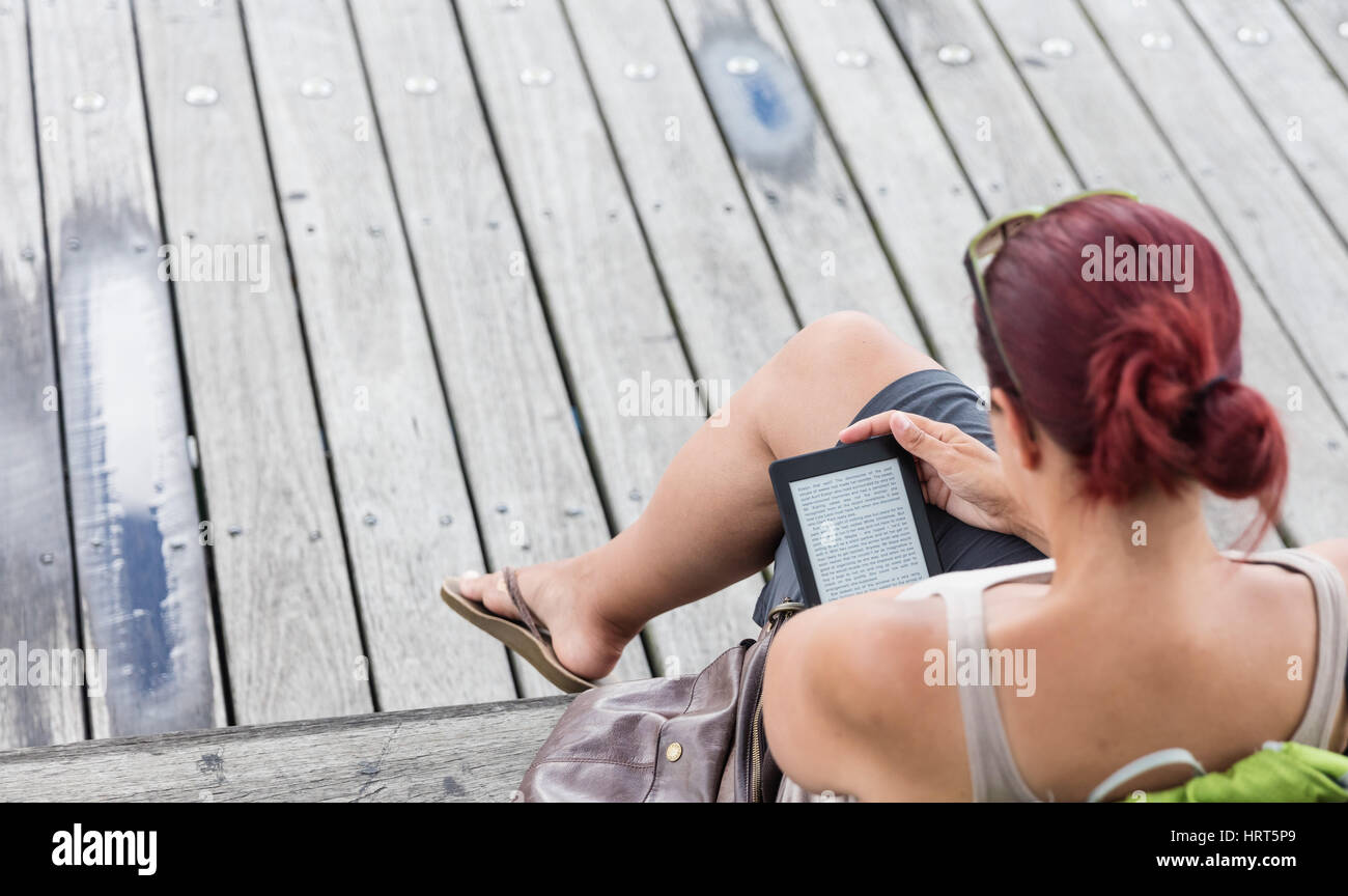 Eine Frau liest ihr Kindle von der Promenade Stockbild