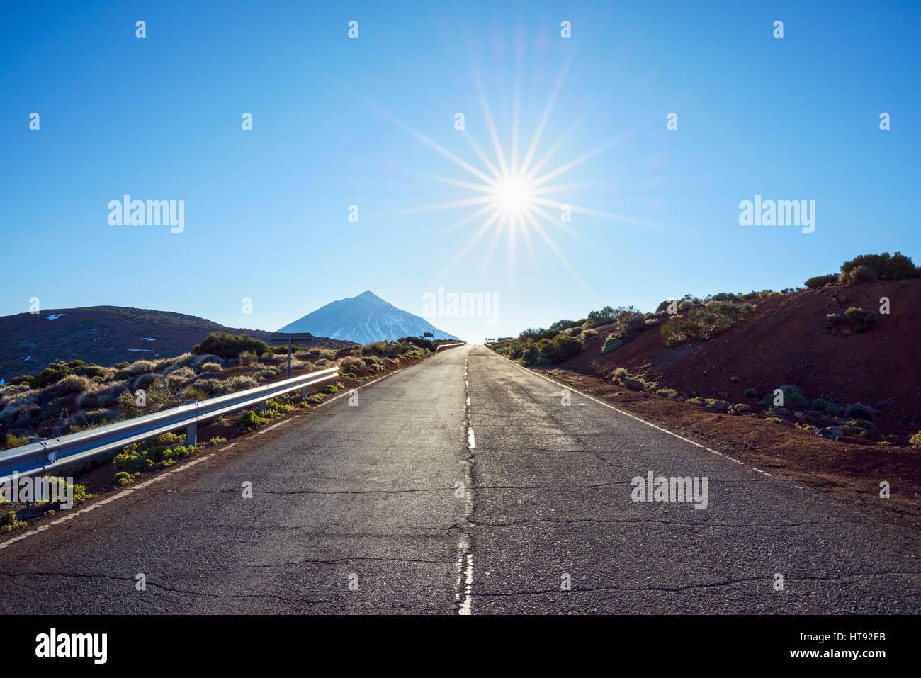 Straße mit Berg Pico del Teide und Sonne, Parque Nacional del Teide, Teneriffa, Kanarische Inseln, Spanien Stockbild