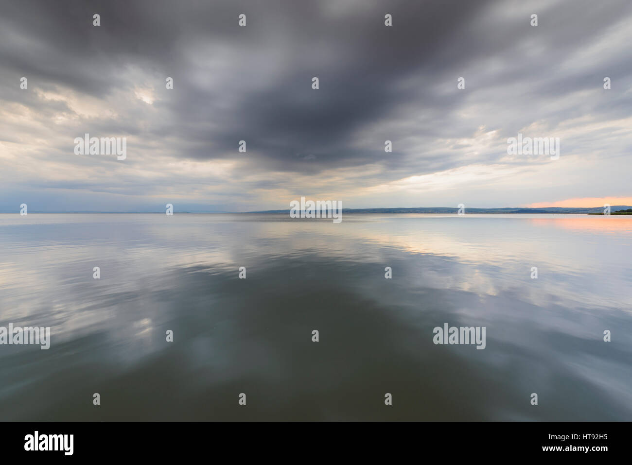 Wolken reflektieren im Neusiedlersee bei Sonnenuntergang auf Weiden, Burgenland, Österreich Stockbild