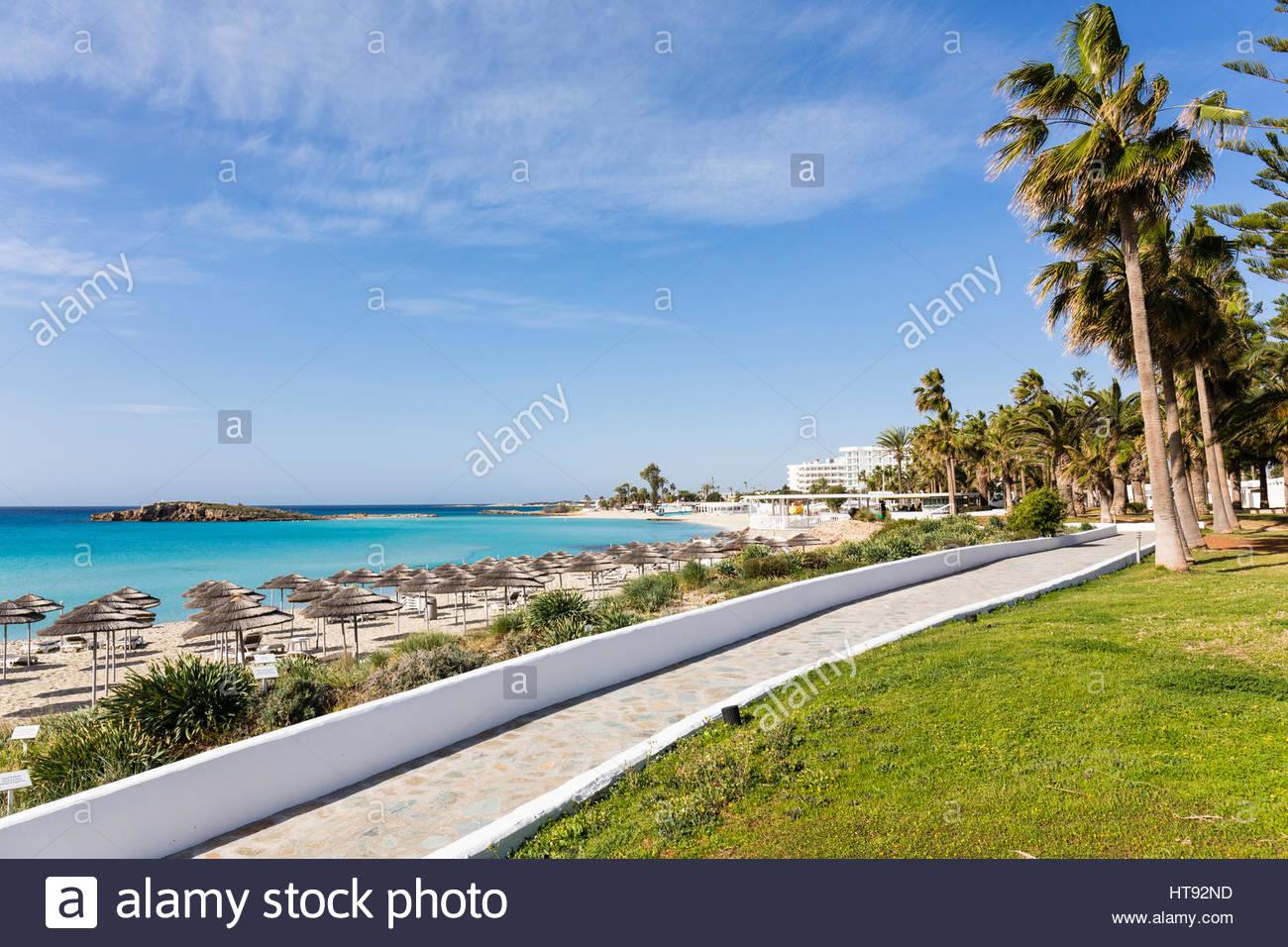 Sonnenschirme am Nissi Strand Nissi Beach Resort mit steinernen Steg in Agia Napa, Zypern Stockbild