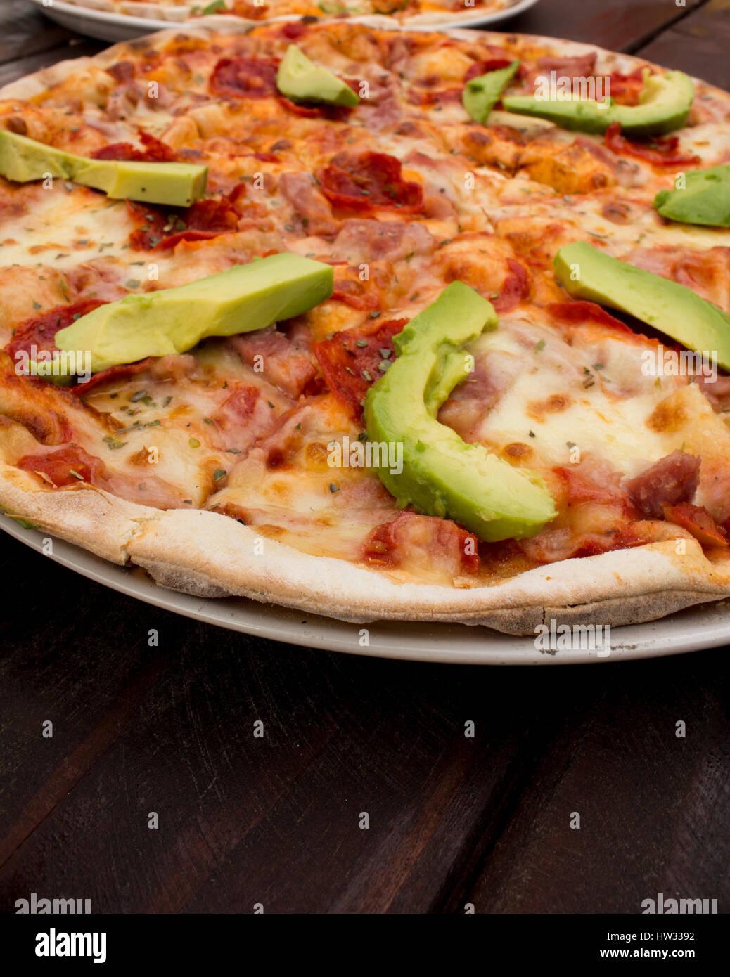 Pizza auf dunklen hölzernen Tischplatte mit frischen Zutaten Stockbild