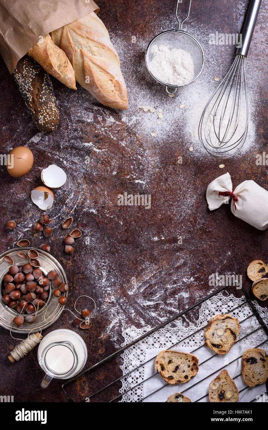 Backwaren - Brot, Baguette, Kekse über rustikale Hintergrund. Backzutaten - Mehl, Nüssen, Eiern, Milch. Stockbild