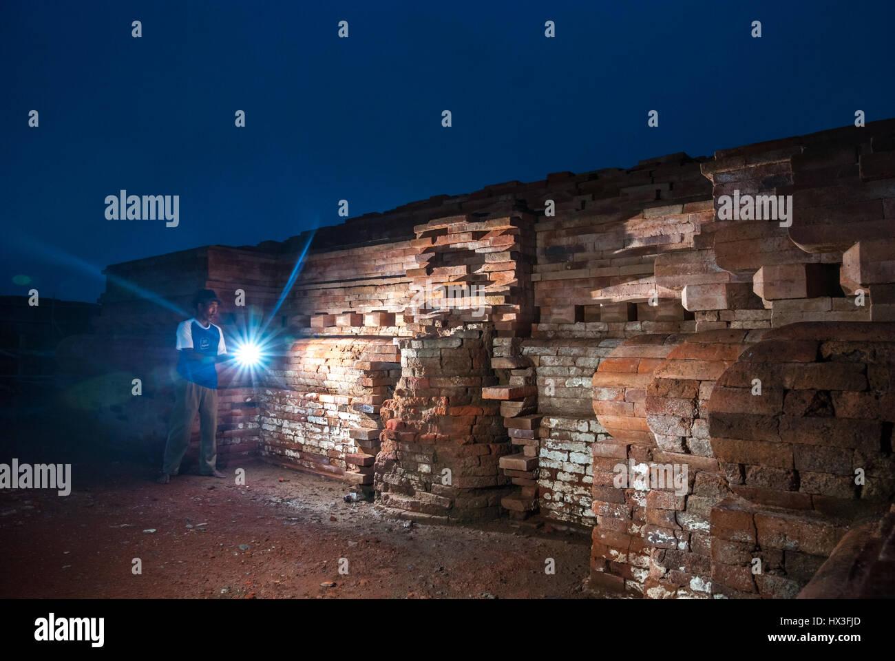 Ein Mann mit einer Taschenlampe in Richtung der Wand des Blandongan Tempels während der Zeit des Wiederaufbaus Stockbild