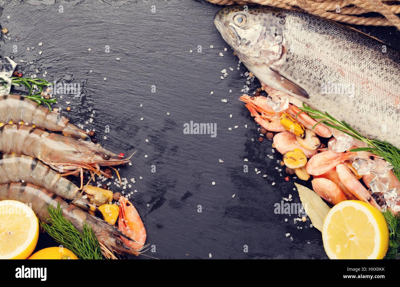 Frische, rohe Meeresfrüchte mit Gewürzen auf schwarzem Stein. Draufsicht mit Textfreiraum. Getönten Stockbild